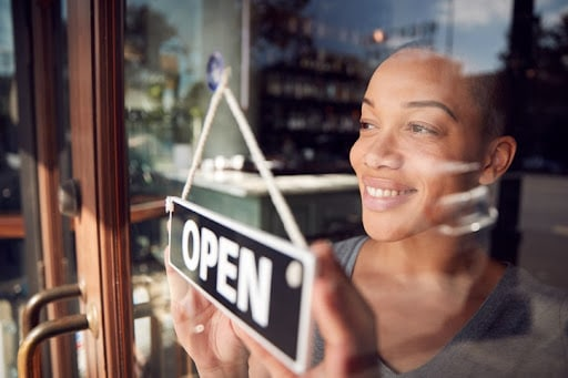 Restaurants are beginning to reopen after COVID. But many will have to adjust to recurring new costs and industry changes long-term. Happy woman in a restaurant window putting up an open sign.